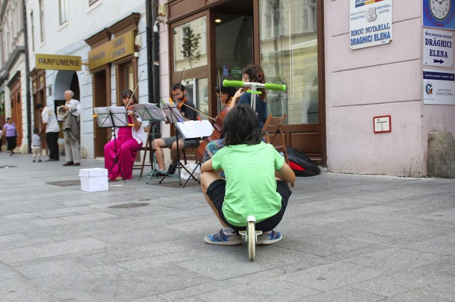 Un niño observa a los músicos callejeros en Sibiu